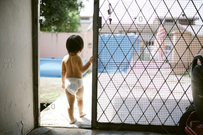 Boy in diaper looking out sliding door