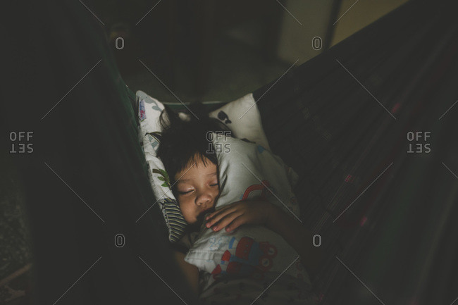 Boy asleep in hammock inside home