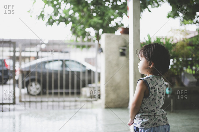 Child staring out at front gate