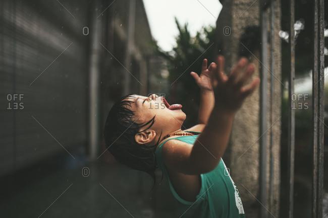 Happy child tasting rain