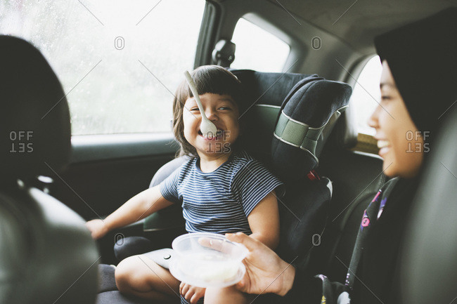 Child being goofy with spoon in car