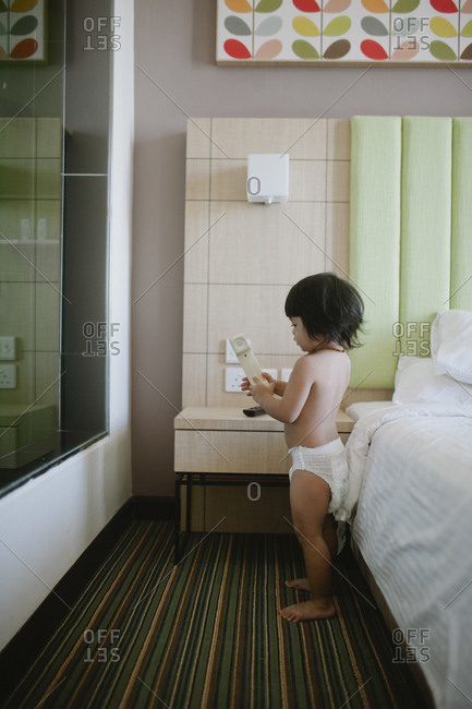 Child in diaper holding phone