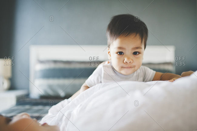 Boy looking over woman on bed