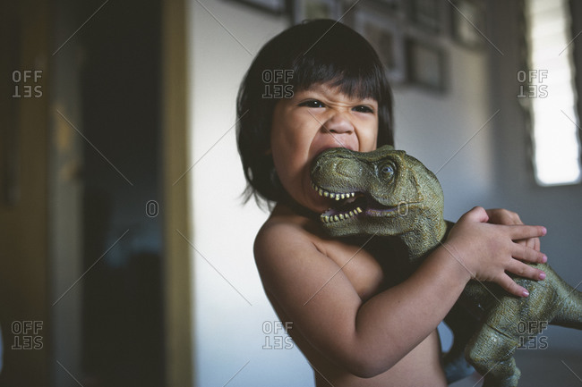 Child biting a toy dinosaur