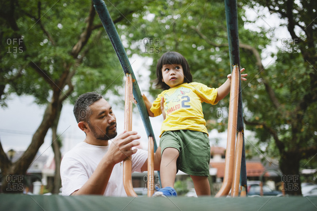 Dad helping child climb jungle gym