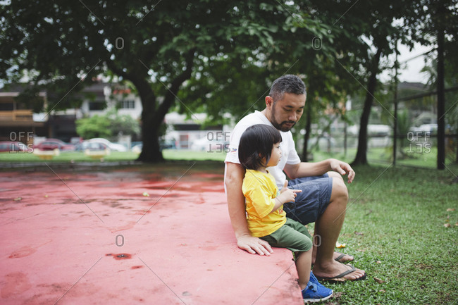 Dad and boy sitting together in park
