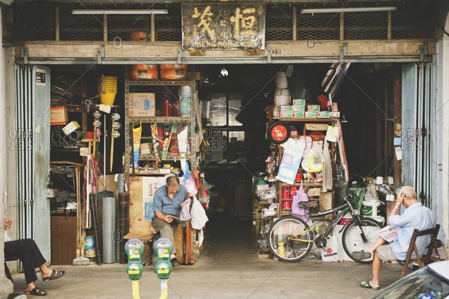 kota bharu, Malaysia - April 27, 2014: Men sitting outside shop in Malaysia