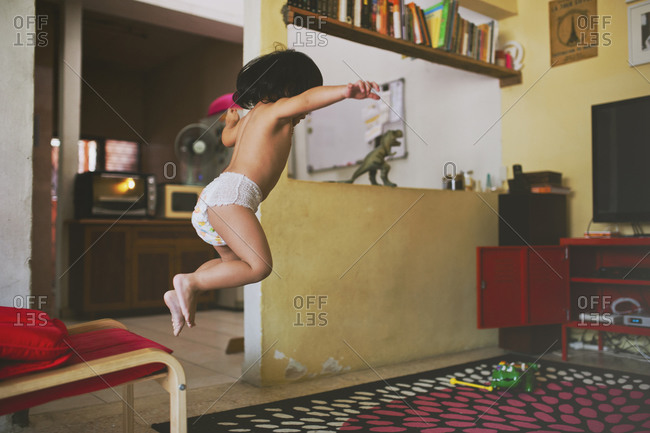 Child in diaper leaping from chair