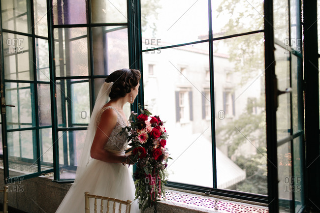 Bride holding a bouquet of flowers and looking out the window