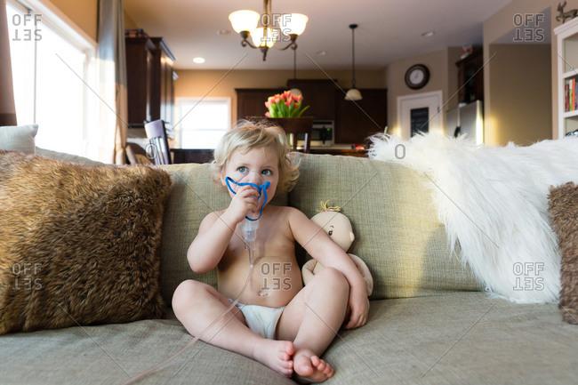 Little girl using nebulizer for breathing treatment