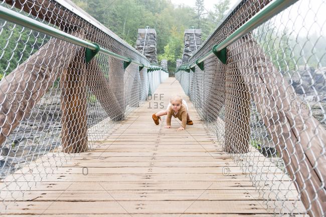 Baby crawling on a bridge