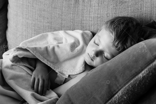 Little boy sleeping on a couch in black and white