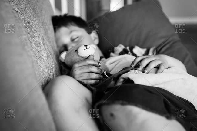 Little boy sleeping on a couch holding a teddy bear in black and white