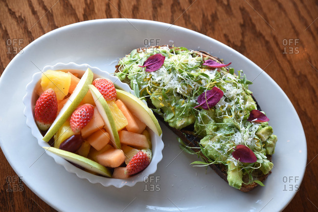 Avocado crostini served with mixed fruit dish