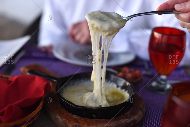 Person holding spoon full of melted cheese