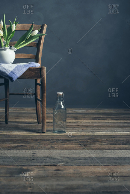 Still life of a wood chair with tulips and bottle in empty room