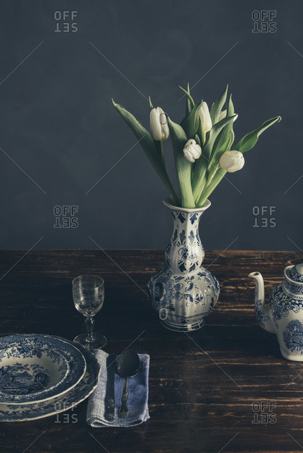 Still life of a vase of tulips and place setting on a wood table