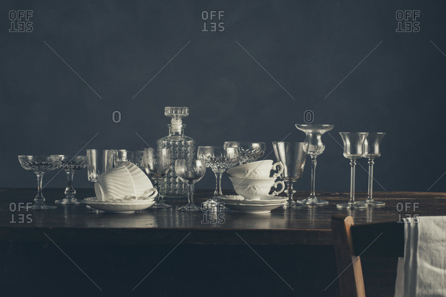 Still life of glass stemware and white cups on a wood table