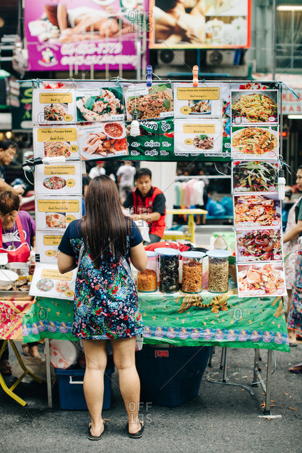 Woman ordering Thai food from a street vendor