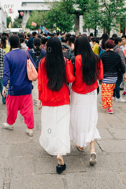Two women walking through a crowd in the same outfit