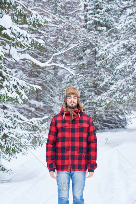 Man in a plaid coat standing in a snowy forest