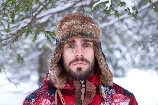 Man in a plaid coat and ear flap hat standing in a snowy forest