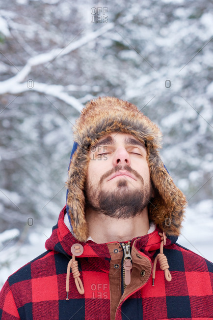 Man in a plaid coat standing with his eyes closed in a forest