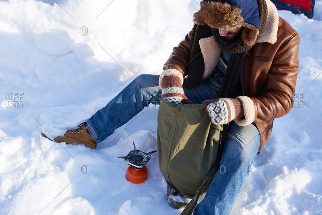 Man sitting in the snow unpacking food items