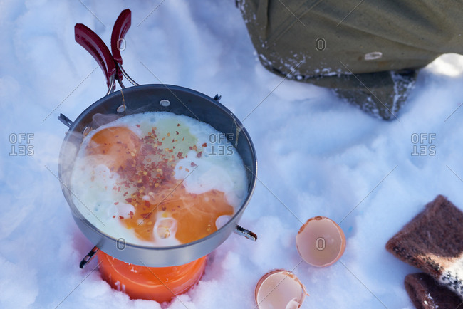 Eggs cooking over a single burner campstove