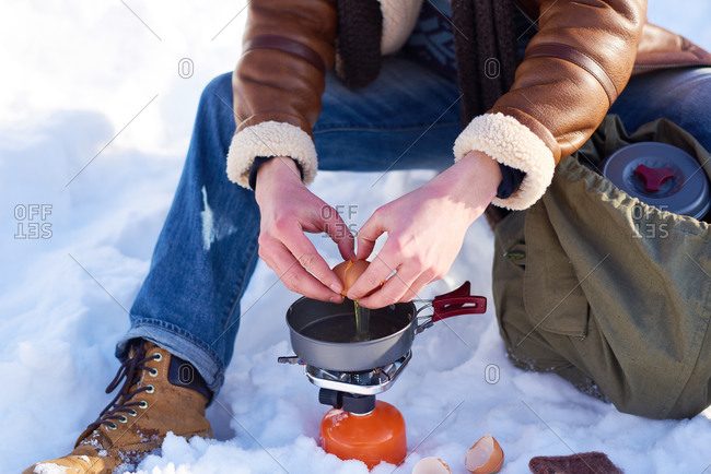 Man cracking eggs over a campstove in the snow