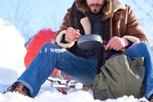 Man eating a meal cooked on a campstove in the snow