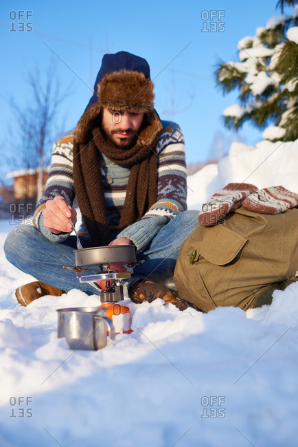 Man sitting in the snow with a sack cooking food over a campstove