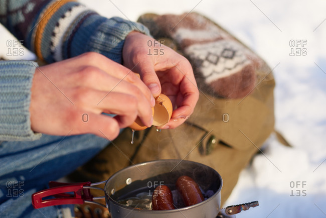 Man making eggs and sausages over a campstove in the snow