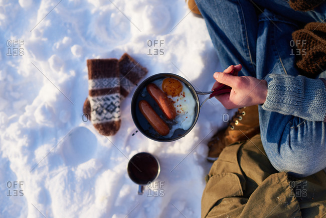 Man holding a pot with breakfast in the snow