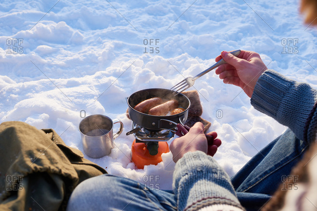 Man stirring sausages in a pot in the snow