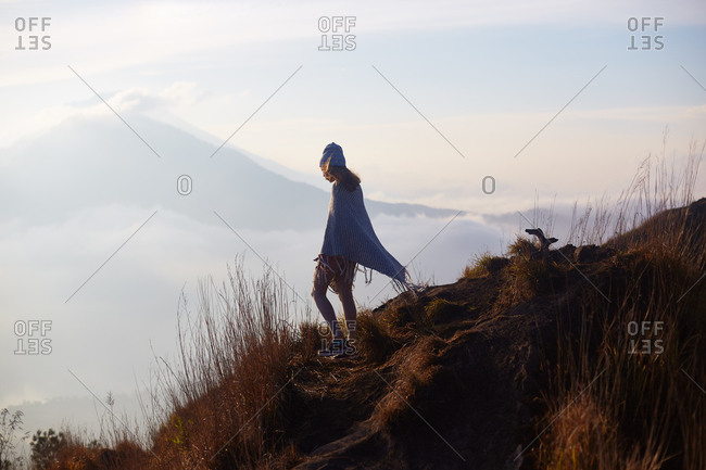 Young woman in a cape on a hillside