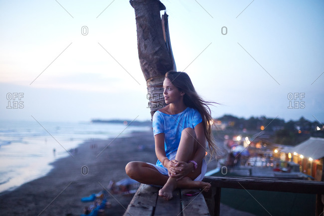 Young woman sitting on a wooden bench overlooking the ocean