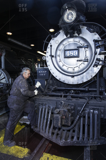 Chama, New Mexico - January 28, 2011: Man restoring an antique train at the Cumbres and Toltec Narrow railyard, Chama, New Mexico