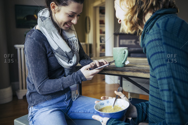 Two woman seated at breakfast table together with smartphone