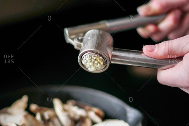 Hands using a garlic press to crush garlic