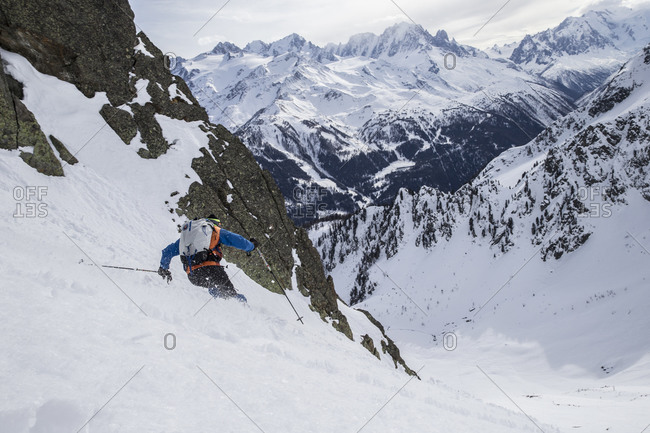Freeride skier in the Swiss wilderness facing the French alps