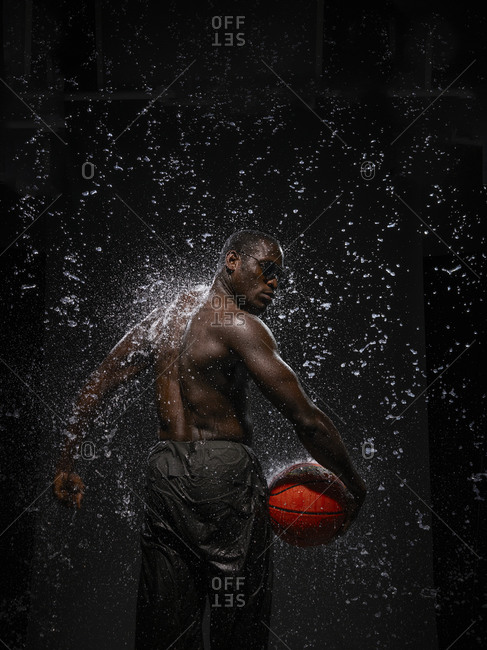 A man holding a basketball surrounded by splashing water