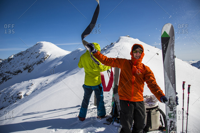 Skiers at the top of a mountain plan their descent in Whistler, British Columbia, Canada