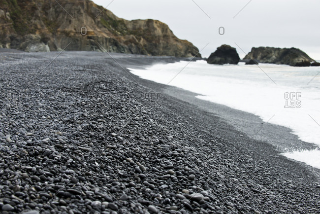 Black rocks line the shore of a beach in northern California