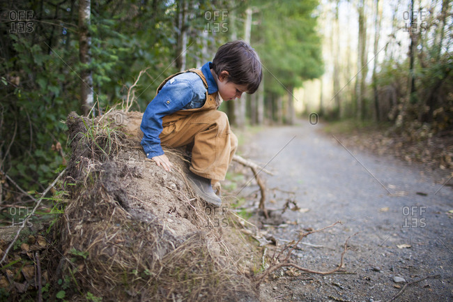 A young boy carefully plans to jump off a pile of dirt while playing outside