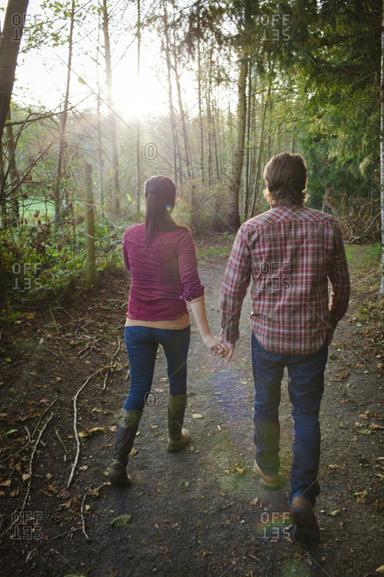 A young couple hold hands while walking together at a local park