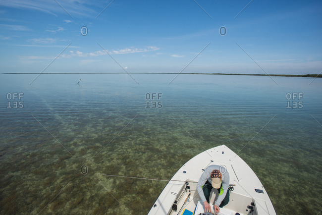Fly fisherman on a flats boat sorting gear in the Florida Bay inside Everglades National Park, Florida