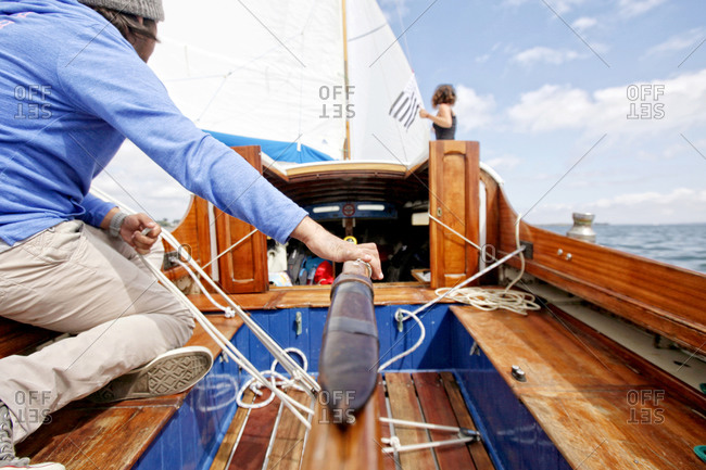 Man and woman working on a sailboat