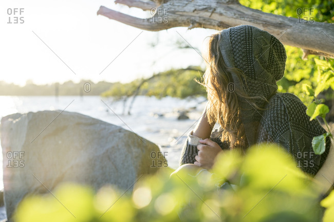 Woman in knitted hooding looking over a lake