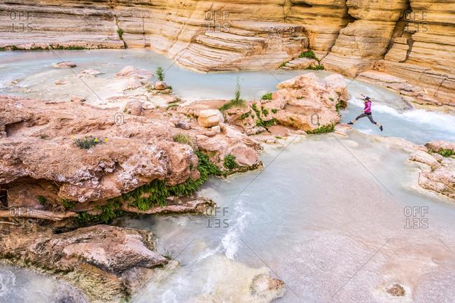 Woman leaping over Havasu Creek